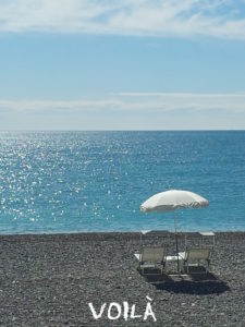 2 white chairs and an parasol in fromt of the sea under a sunny blue sky