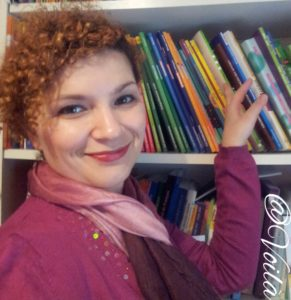Young woman, smiling, in front of a bookshelf