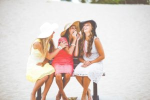 3 girls on a bench talking and laughing