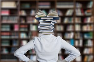 Female student with the head replaced by a pile of books