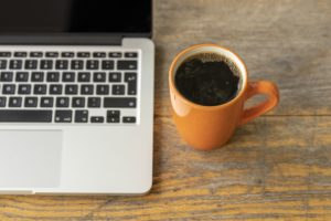A silver laptop with an orange espresso cup