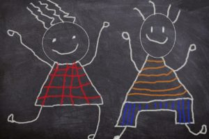 Drawing on a black board: 2 children